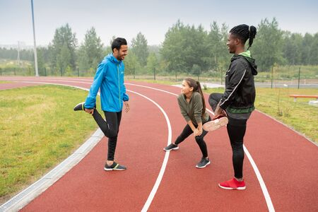 Group of young intercultural athletes doing wam-up exercises on racetracks Standard-Bild