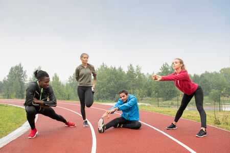 Young healthy intercultural men and women in sportswear doing physical exercises Standard-Bild