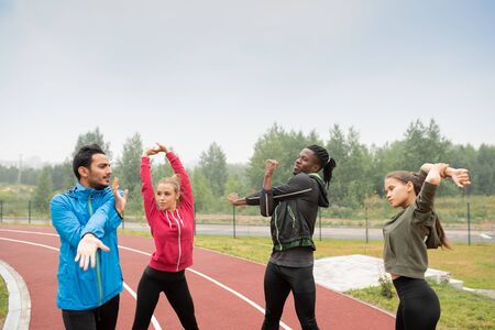 Group of young intercultural friends in activewear doing warming up exercises Standard-Bild