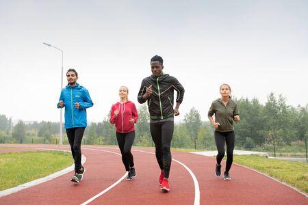 Group of young intercultural sportsmen and sportswomen running marathon