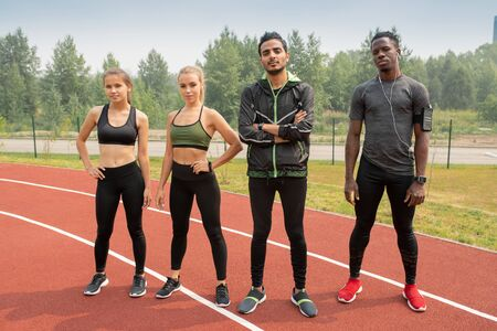 Row of young intercultural athletes in sportswear standing on racetracks