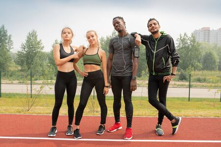 Four young friendly intercultural people in sportswear standing on racetrack