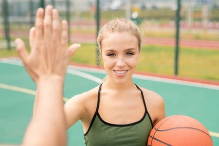 Pretty young blonde woman in activewear giving high-five to her friend Stock fotó