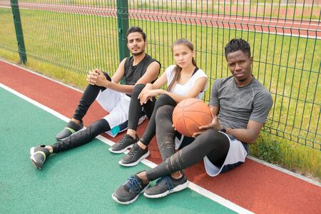 Three young athletes in sportswear sitting on outdoor basketball court by net Stock fotó