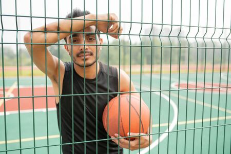Serious male basketball player with ball standing against net Stock fotó