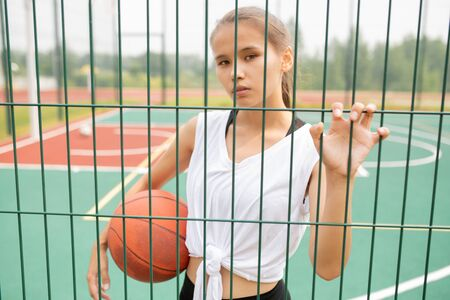Pretty girl in activewear holding ball while looking at you through sports net Фото со стока