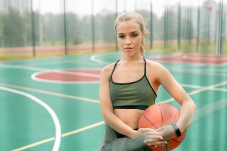 Pretty young woman in activewear holding ball for playing basketball