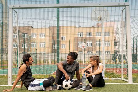 Three young intercultural friendly soccer players sitting by net on green grass