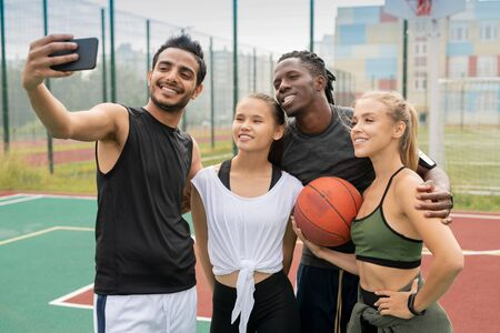 Group of young intercultural friends in sportswear making selfie on court