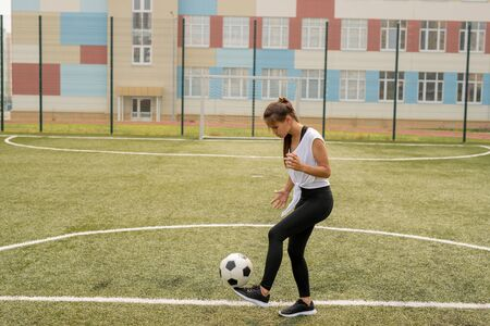 Young sportswoman in activewear kicking soccer ball while training on the field Фото со стока