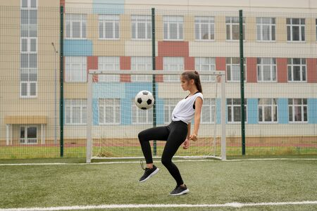 Young sportswoman in leggins, sneakers and t-shirt training to play soccer