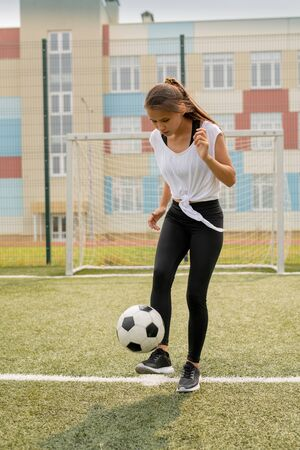 Fit girl in sportswear standing on sports field while kicking soccer ball