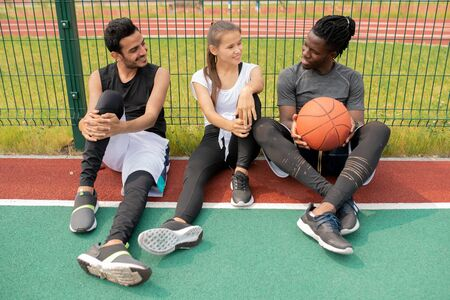 Two guys and girl in sportswear chatting while sitting on playground