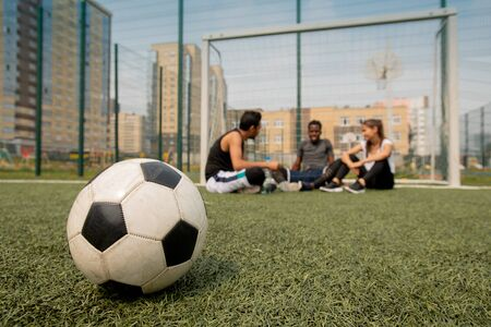 Soccer ball lying on the field or playground on background of players