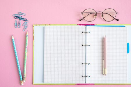 Open copybook with blank pages, pen, two pencils, clips and eyeglasses
