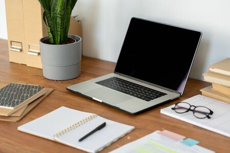 Workplace of home office employee with laptop, eyeglasses, open notebook and pen