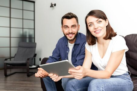 Positive couple using wifi at home