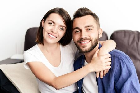 Portrait of cheerful young beautiful couple sitting on sofa