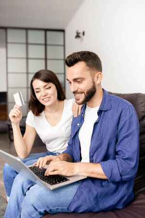 Cheerful young couple sitting on sofa in living room