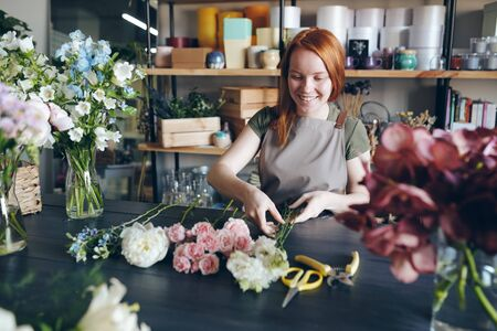 Cheerful beautiful redhead florist in apron standing at table