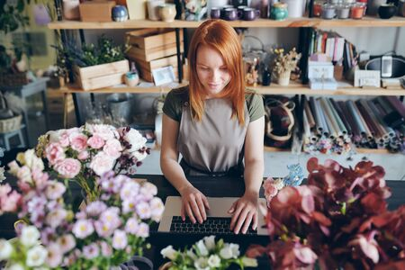 Pretty florist working with social media of flower shop Stok Fotoğraf - 130735337