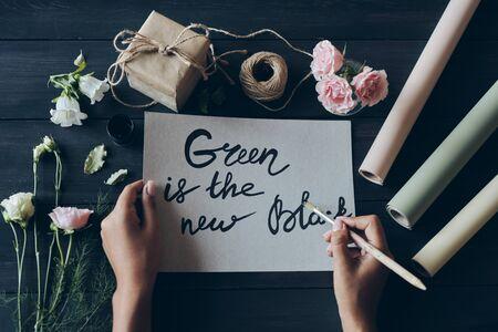 Designer writing calligraphy with paintbrush