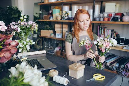 Young woman creating beautiful floral arrangement Archivio Fotografico - 130735509