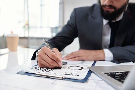 Businessman Writing on Clipboard Closeup