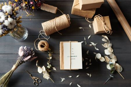 Above view of packaged gifts on table with messy petals Reklamní fotografie