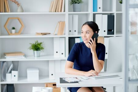 Pretty young brunette businesswoman with smartphone calling clients