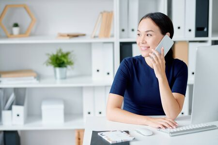 Young manager in elegant dark blue dress consulting clients on the phone Stock Photo