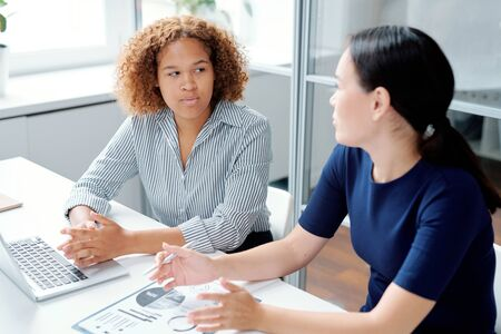 Young serious mixed-race accountant looking at her colleague explanation Stock fotó