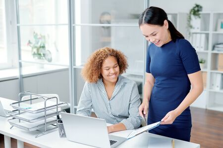 One of female managers pointing at financial paper while showing it to colleague Stock fotó