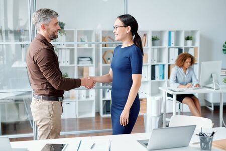Young successful colleagues or business partners shaking hands by workplace