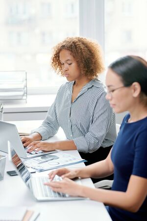 Young serious mixed-race banker touching keys of laptop keypad at workplace