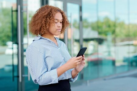 Serious young curly businesswoman scrolling in smartphone outdoors