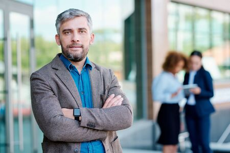Confident leader of business team standing in front of camera by office building