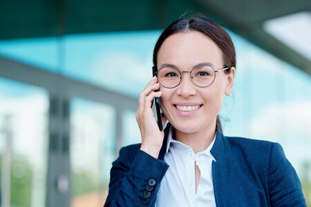 Elegant young female employee with toothy smile holding smartphone by ear