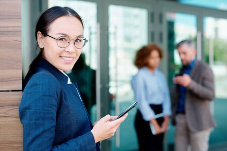 Elegant businesswoman with smartphone standing by corner of office building