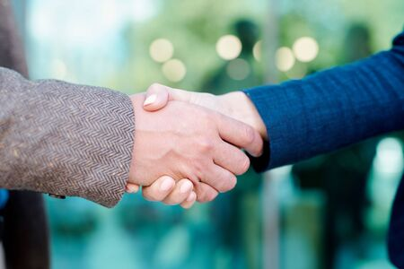Hands of young contemporary employees in handshake symbolizing partnership Stock Photo