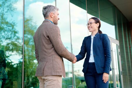 Happy young businesswoman shaking hand of her client after making deal
