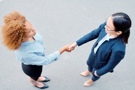 View of two multicultural businesswomen shaking hands and looking at one another