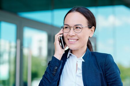 Young smiling brunette businesswoman discussing working moments on smartphone