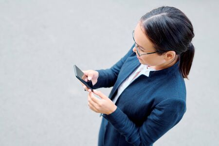 Young attractive businesswoman with mobile phone texting or scrolling
