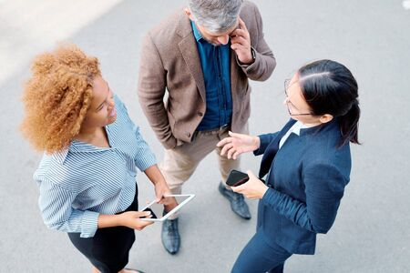 Group of young multicultural colleagues or business partners with gadgets