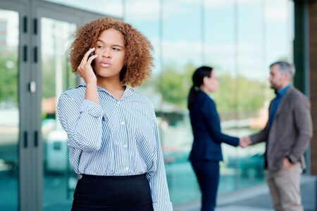 Young serious businesswoman talking to one of partners on the phone outdoors Stock Photo