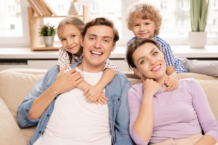 Young cheerful family of father, mother and two cute siblings Stock Photo