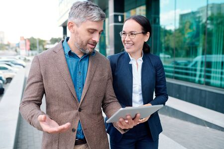 Confident businessman discussing online data with his colleague on the move Stock Photo