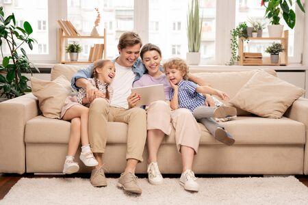 Junge fröhliche zufällige Familie mit zwei Kindern und Paaren, die lustige Videos ansehen
