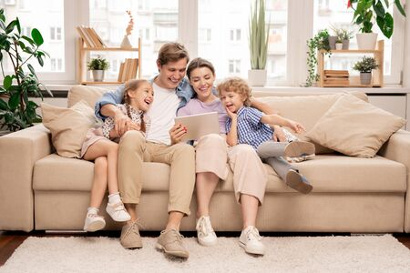 Young joyful casual family of two kids and couple watching funny video